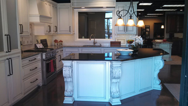white acanthus leaf corbel on white kitchen island with black marble counter triangle cabinet cures